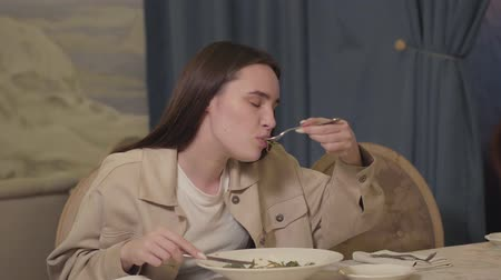 listens : Pretty woman with long hair eating noodles with greens and vegetable sitting at the table in the restaurant. Lonely lady enjoying her meal in the modern restaurant. Food serving