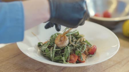 iştah : Tasty salad with arugula, king shrimps, tomato and olive oil in the big white plate on the table in the kitchen. Hand of the chef decorating food with the lemon slice. Food serving in the modern restaurant Stok Video