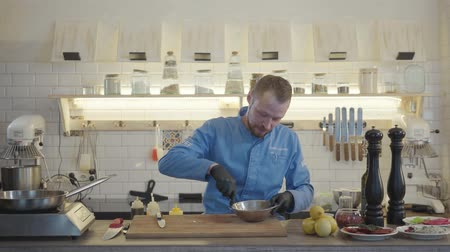 kitchenware : Chef man in restaurant uniform and black gloves stand in the modern kitchen with many kitchen utensils around and mixing in bowl a small pieces of tuna fish. Stock Footage