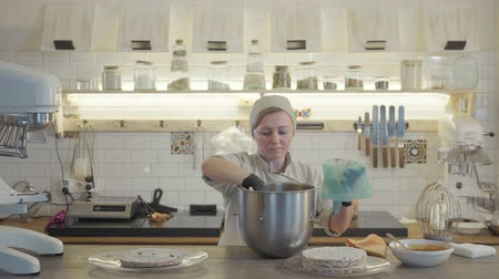 кухонная посуда : Woman in uniform and black gloves stand in the modern kitchen with many kitchen utensils around and put white cream inside pastry bag. Female will make a cream decoration for a cake.
