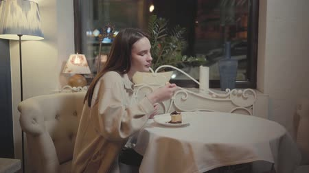 mouth watering : Cute young girl eating fresh mouth-watering chocolate cheesecake or tiramisu in beautiful restaurant Stock Footage