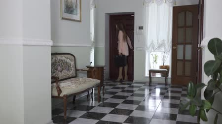 kostka : Pretty young woman entering the house, taking off shoes and throwing them away. Tired girl back home. Beautiful room interior with wooden furniture and black and white tile on the floor