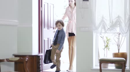 como : Young beautiful girl open a door and come inside home with tired small brother who carring big schoolbag