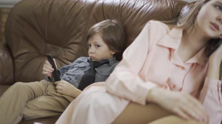 fejlesztése : Small boy sit on the sofa with remote control and young sister sit near and talk to mobile phone. Brother and sister relations
