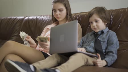 riches : Serious older sister and younger little brother sitting on leather sofa. The boy holding laptop, the girl counting money. Kids as adults. Children of rich parents. Wellness concept