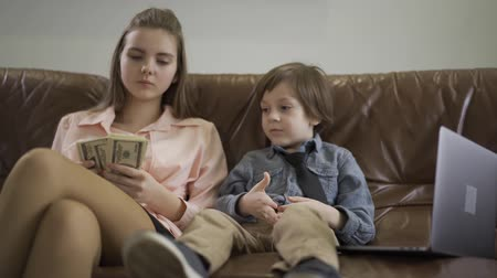 mafia : Serious older sister and younger little brother sitting on the leather sofa, laptop is near. The girl counting money and gives some to the boy. Kids as adults. Children of rich parents. Wellness concept Stock Footage
