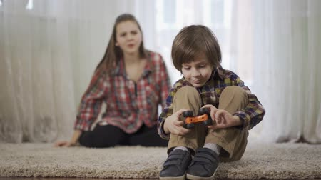 nanny : Older sister scolds younger brother who is playing with the toy car sitting on the floor on the fluffy carpet in the foreground of the girl. Age difference, the problem in the relationship Stock Footage