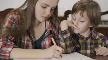 домашнее задание : Sister helping her brother with home assignment. Portrait of two cute children working on homework together. Family relationship. Стоковые видеозаписи