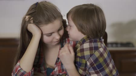 puericultura : Close-up portrait adorable small boy whispering secret to elder sister girl. Loving friendly family, happy kids. Stock Footage