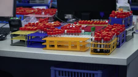 szczepienia : The table with many racks for test tubes close up. Female putting the tube in the rack and walking away. Conducting research in the laboratory. Science, profession, healthcare. Working process. Slow motion