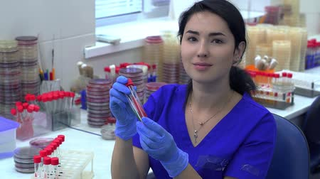 consistency : Young woman in blue uniform taking two tubes from a rack for test tubes and checking color and consistency of fluid, then looking in camera smiling. Conducting research in laboratory. Science, profession, healthcare. Slow motion