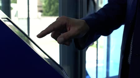 ticket machine : A man takes ticket to the queue at the clinic. Hand of the man in the suit using terminal close up. The man touching the screan with his finger. Servise of the client