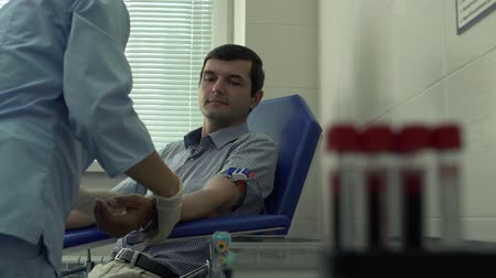 manşet : Hands of the nurse preparing to take the blood of the patient sitting on the armchair in the background. Blurred test tubes with labels are in the foreground. Blood test. Science, profession, healthcare Stok Video