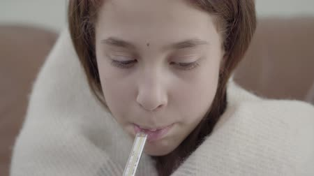medical thermometer : Portrait of teenage girl wrapped in a blanket takes a thermometer in her mouth and measures the temperature. The girl feels bad, she is ill and has fever. Concept of healthcare, treatment