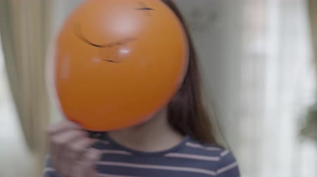 happiness symbol : A funny cute girl hold orange baloon with emoji and making same emoji face with wink and tongue emoticon Stock Footage