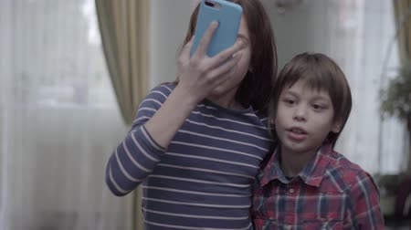 аналогичный : Kids, sister and brother making selfie at home at mobile phone, girl showing tongue and boy is laughing