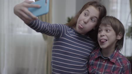 аналогичный : Kids, sister and brother making selfie at home at mobile phone, girl showing tongue and boy is laughing.