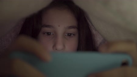 genius : Cute teenage girl playing her cellphone lying under the blanket close up. Bedtime. The blue light has negative effect on the childs eyes