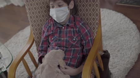 ношение : Portrait a sick boy with a medical bandage on his face swaying in his chair, holding a soft toy in his hands at home. Стоковые видеозаписи