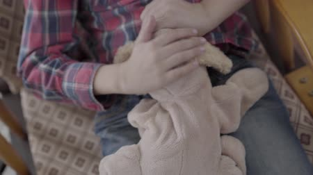 influenza : Unrecognized boy swaying in his chair, holding a soft toy in his hands close-up.