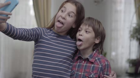 denemek : Older sister taking a selfie with her younger brother close up. The children make faces, pose try to look funny. Carefree childhood. Happy family Stok Video
