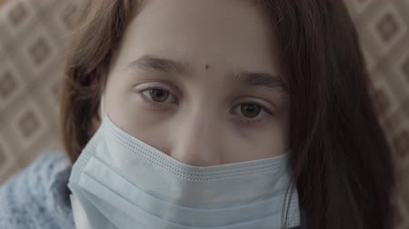 čelo : The sad sick girl with a sterile mask on her face looking into the camera close up. The girl has an infectious disease. Concept of healthcare Dostupné videozáznamy