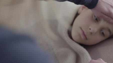 čelo : The sad teenage girl wrapped in a blanket lying in bed while mother hand touching her forehead looking on the thermometer. The girl feels bad, she is ill and has a fever. Concept of healthcare, treatment Dostupné videozáznamy