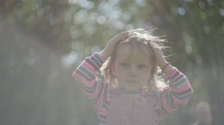 rainha : The cute little girl in the crown upside down on her head in the foreground looking forward. Adorable funny princess playing outdoors. Blurred mom in the background Stock Footage