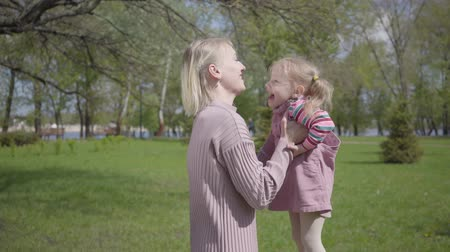 детская площадка : Portrait young mother spinning the daughter on hands on nature on spring day. Woman and kid playing in the park. Joking and having fun. Family vacation in the park outdoor.