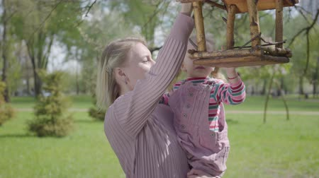 alimentador : Young blond mother hold adorable small daughter and show her bird feeder house in the amazing green park. Loving carring family.
