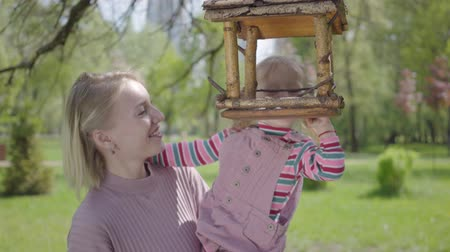 alimentador : Young mother spending time in the park with her daughter. The woman lifting up her little cut girl so she could see bird feeder close up. Active healthy lifestyle, connection with nature
