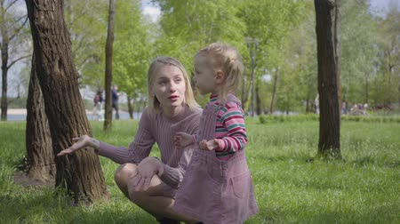 crouch : Cute little girl playing in the park with her mother, pointing with a tiny finger away. The woman explaining to her kid how is the world. Carefree child resting outdoors with one parent. Active healthy lifestyle, connection with nature Stock Footage