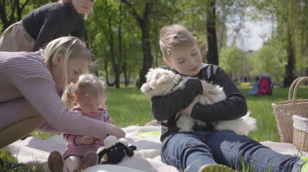 entre : Two young mothers with them kids sit on the blanket in green amazing park on nature on spring day. Mom and son, mother and daughter at picnic. White fluffy dog lie down near. Concept of friendship between families.
