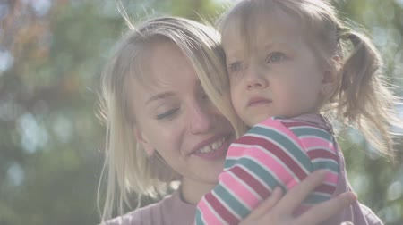 держит : Portrait of young mother and amazing blond daughter at mothers hands in the park