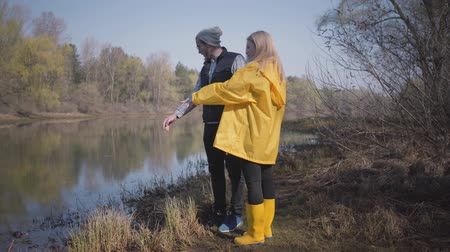 stivali di gomma : Stylish couple looking at the river in the forest. Man wearing vest, hat, sun glasses. Blond woman wearing yellow coat and boots. Filmati Stock