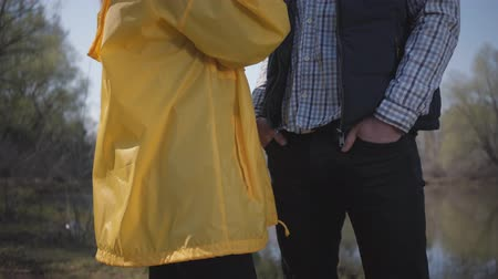 yarık : Young stylish couple walking in nature outside the city near the river. Beautiful blonde girl in a yellow raincoat and slit rubber boots flirts with a bearded guy in a stylish hat. Stok Video