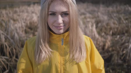 raincoat : Young beautiful blond woman posing near forest with lake. Amazing view.