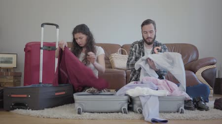 сложить : Bearded man and beautiful woman sitting on the floor and packing them cloth to the big suitcases Стоковые видеозаписи