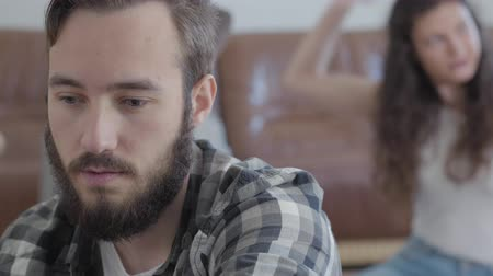 quarreling : Portrait of an offended bearded man sitting in the foreground while his happy wife trying on a scarf on the background. Carefree girl and serious man. Difficulties of understanding in a young family Stock Footage