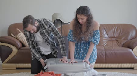 coisas : The man and woman sitting on the floor at home in front of leather sofa, packing a suitcase before travel. There are too many clothes in the suitcase and it does not close. Family packing before a trip