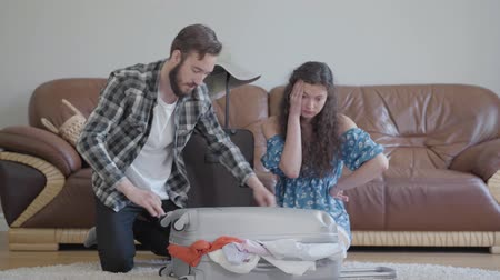 coisas : Nervous man and woman sitting on the floor at home in front of leather sofa, trying to pack a suitcase before travel. There are too many clothes in the suitcase and it does not close. Family packing before the trip