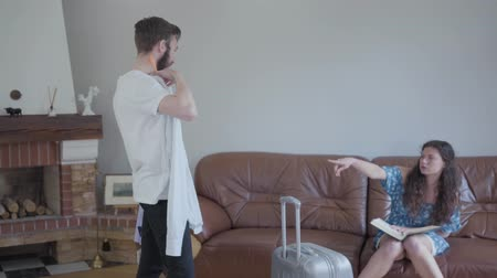 decidir : Young couple packing suitcase, woman choose the shirt for a man. Travelers.