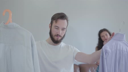casual wear businessman : The handsome bearded man asking his wife advice about which shirt to wear, she chose one and nodding. The husband preparing his clothes before to go for work. Friendly family concept Stock Footage
