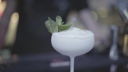 аперитив : Beautiful white glass with a cocktail decorated with mint. Close up.