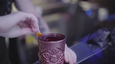 ginástico : Unrecognizable young bartender rubs clay glass of cocktail with the orange peel before serving to the visitor. Night lifestyle, night fun. Barman making alcohol drink