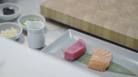 служить : Pieces of tasty salmon and tuna lying on the long plate in the restaurant kitchen, preparing for serving on the table. Healthy food in a modern restaurant, close-up. Little jars with sauces are near Стоковые видеозаписи