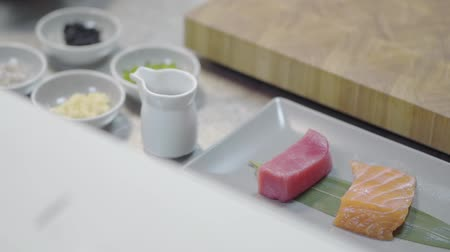 szószok : Pieces of tasty salmon and tuna lying on the long plate in the restaurant kitchen, preparing for serving on the table. Healthy food in a modern restaurant, close-up. Little jars with sauces are near Stock mozgókép
