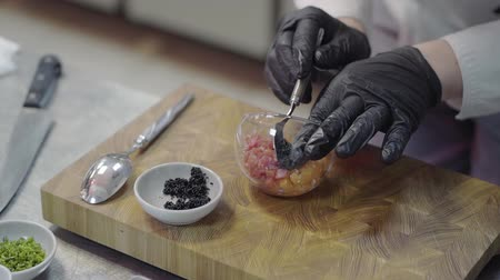kaviár : Chef in white restaurant uniform with black gloves decorating a plate with tuna fish and selmon and put inside a black caviar