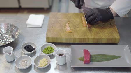 szószok : Hands of chef in white restaurant uniform cutting small salmon fish. Kitchenware around, spice, spoons, tunafish piece, sauces and other ingredients.