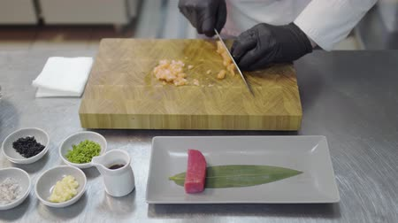 szószok : Hands of chef in white restaurant uniform cutting small salmon fish. Kitchenware around, spice, tunafish piece, sauces and other ingredients.